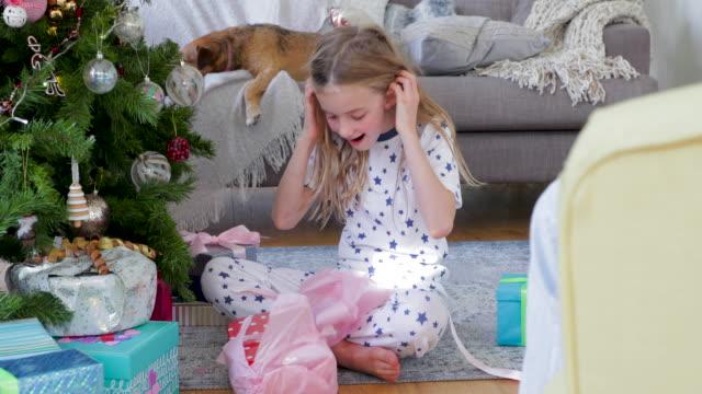クリスマスにクリスマス プレゼントを開ける少女 - クリスマスプレゼント点の映像素材/bロール