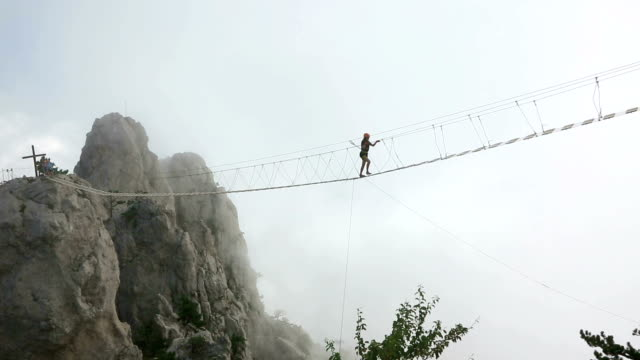 Young girl over abyss Woman walking on the rope bridge over the abyss suspension bridge stock videos & royalty-free footage
