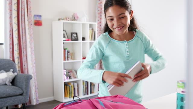 vídeos de stock e filmes b-roll de young girl packing bag ready for school in bedroom - mochila saco