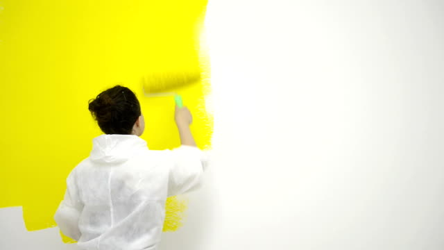 young girl painting white wall with yellow color video hd - painting wall bildbanksvideor och videomaterial från bakom kulisserna
