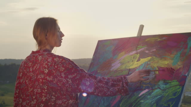 vidéos et rushes de la jeune fille peint l'image dans la nature. gros plan. - toile à peindre