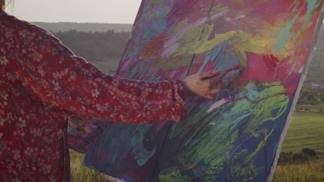 vidéos et rushes de image de peinture de jeune fille. l'artiste se tient sur la colline et regarde le paysage avec le pinceau dans ses mains. - toile à peindre