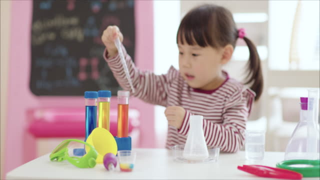 young girl play bubbling volcano science experiment