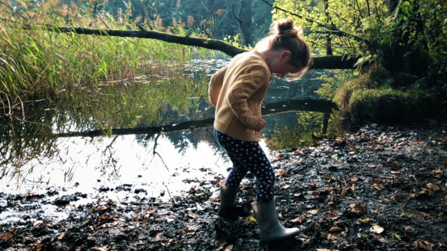 young girl playing by the side of a lake in a muddy puddle - esploratore video stock e b–roll
