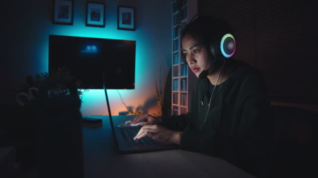 Young girl playing computer game on laptop at night Teenager asian woman playing games on a laptop at home gamer stock videos & royalty-free footage