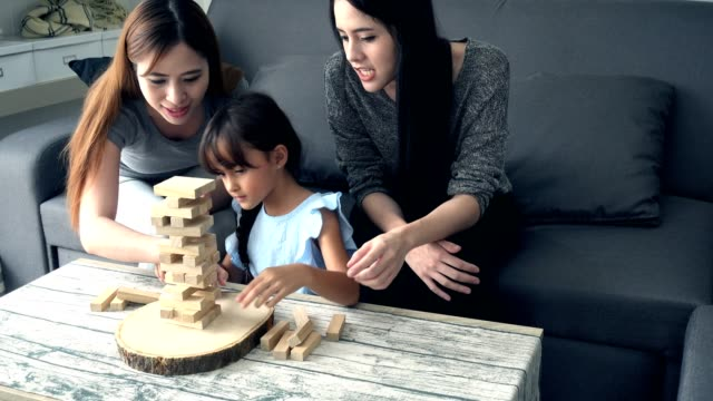 Young girl playing game with mother and asian nanny in living room. video