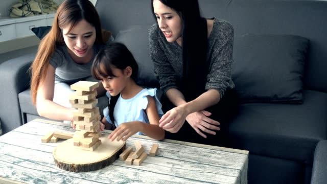 若い女の子が居間で母とアジアの乳母とゲームをプレイします。 ビデオ