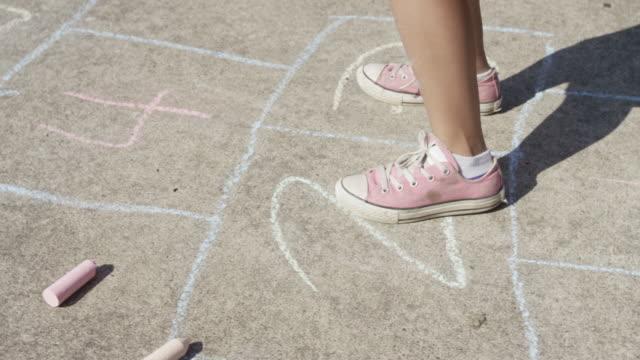 Young girl playing Hopscotch, closeup of feet video