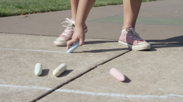 Young girl playing Hopscotch, drawing with chalk video