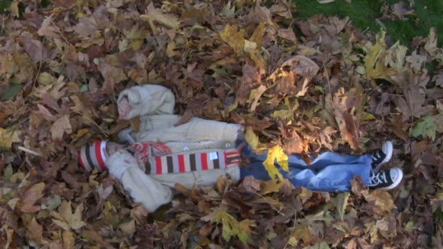 vidéos et rushes de jeune fille jouant dans les feuilles - entassé