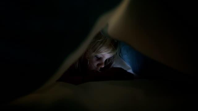 young girl playing on cell phone under duvet - kołdra filmów i materiałów b-roll
