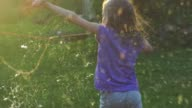 istock Young Girl Playing with Giant Soap Bubbles at Sunset Backlit View 1271156269