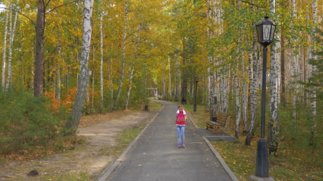 Young girl plugged her ears with her hands and walked along the yellow avenue in the autumn park. video