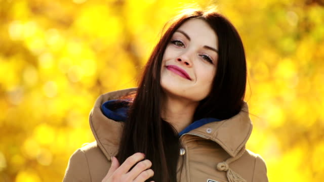 young girl posing on a background of yellow leaves video