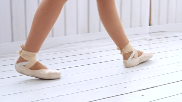 A young girl practicing ballroom dancing in a bright cozy room. A young girl practices ballroom dancing in a bright, cozy room and falls. Close view of the legs. ballet dancer stock videos & royalty-free footage