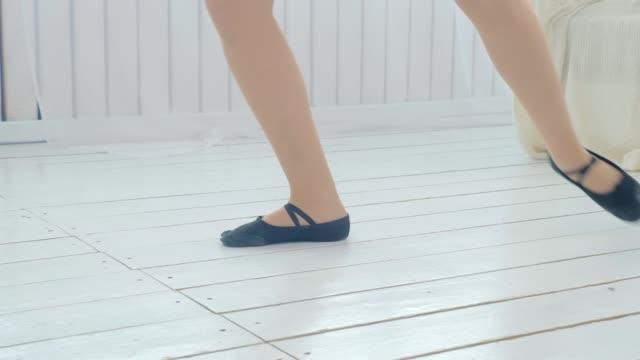 明るい居心地の良い部屋でボールルームダンスを練習している若い女の子。 - チュール生地点の映像素材/bロール