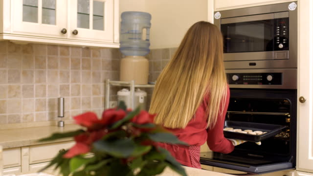 Young girl put the baking tray with cookies in the oven video