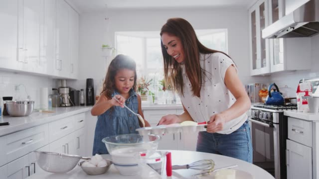 Young girl putting cake mix into cake forms while baking with her mother in the kitchen, close up Young girl putting cake mix into cake forms while baking with her mother in the kitchen, close up mixing bowl stock videos & royalty-free footage
