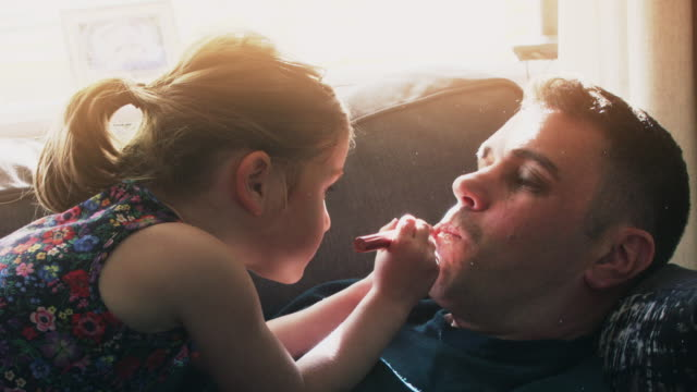 young girl putting makeup on daddy for a funny makeover game - córka filmów i materiałów b-roll