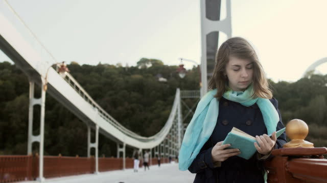 Young girl read book on the bridge video