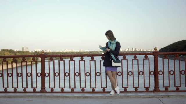 Young girl read the book at the bridge on river background video