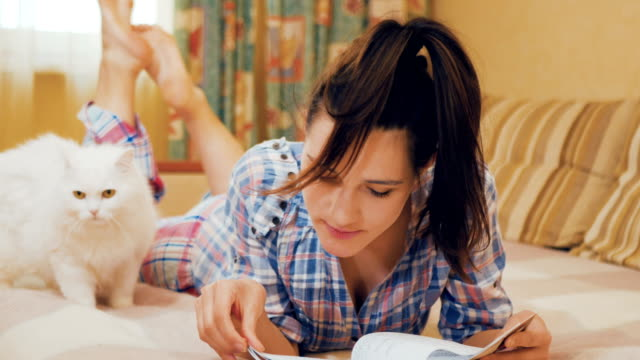 Young girl read the notes in notebook, preparing to exam; white cat near girl video