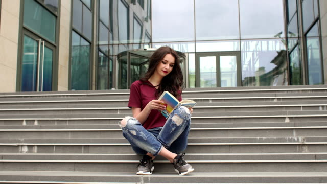 Junges Mädchen in einem Buch sitzen auf Stufen bei city – Video