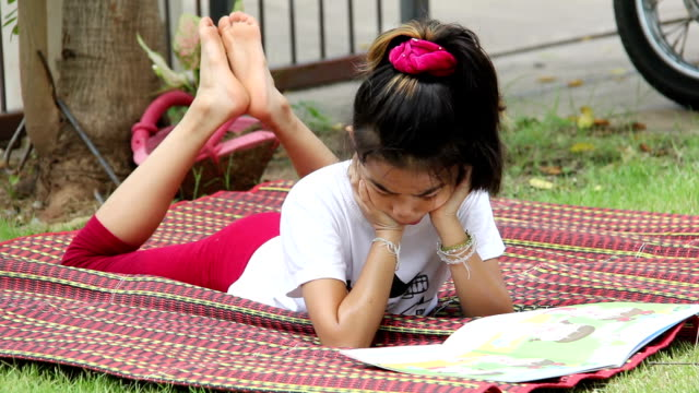young girl reading in garden video