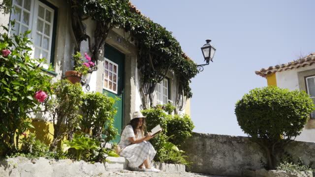 vídeos de stock e filmes b-roll de young girl relax on doorstep of cozy house - ivy building