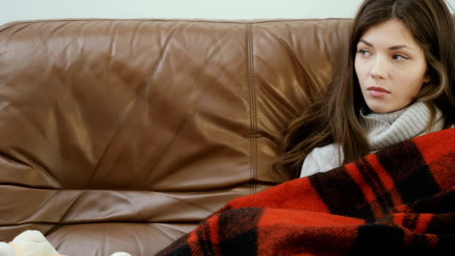 Young girl relaxes on the sofa under the plaid video