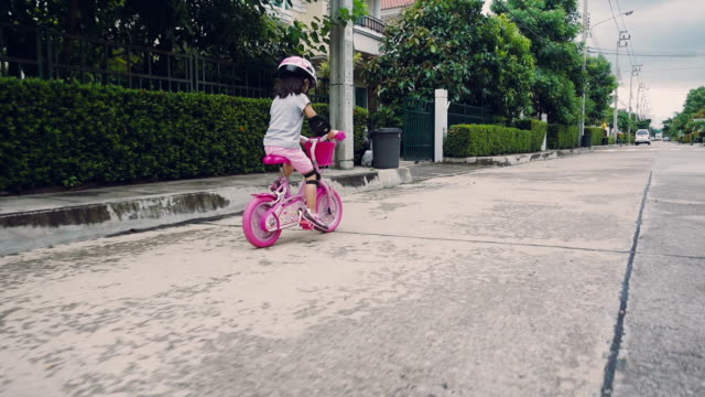A young girl riding her bike outside on a sunny day near the home, Thailand video