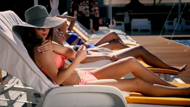 junges mädchen reibt den körper durch sonnencreme in der nähe von schwimmbad - sun chair stock-videos und b-roll-filmmaterial