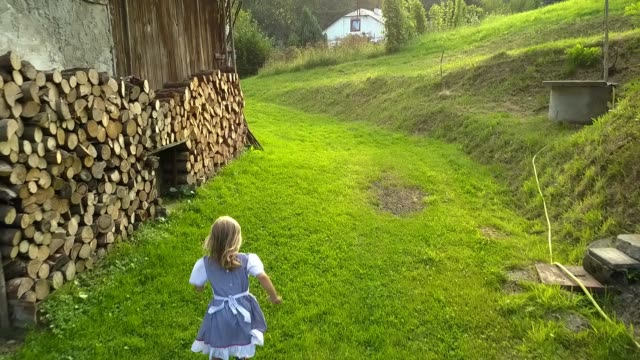 young girl running by farm barn slow motion - cowgirl video stock e b–roll