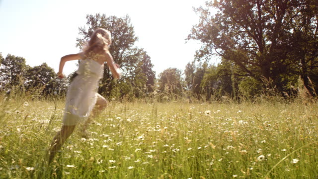 SLO MO Young girl running in high grass on a sunny day video