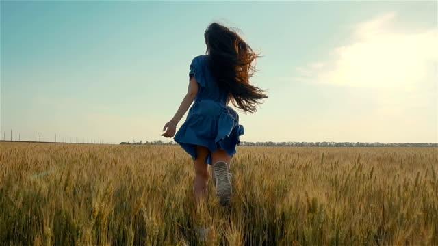 ung flicka springer i slow motion över fältet. vacker fri kvinna njuter av naturen i varmt solsken i vete på solnedgången bakgrund - klänning bildbanksvideor och videomaterial från bakom kulisserna
