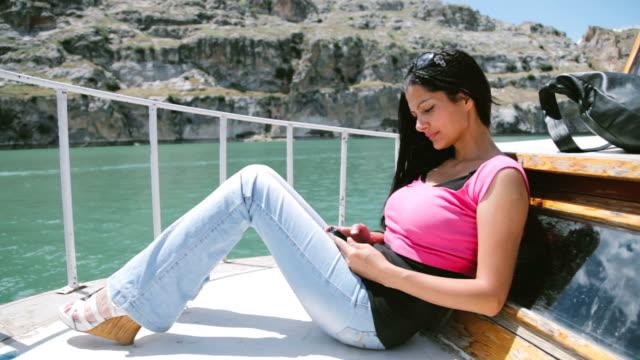 Young Girl Sailing texting wity smartphone in A Yacht video
