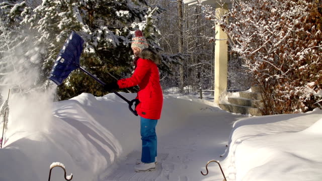 Young girl Shoveling snow on walkway video