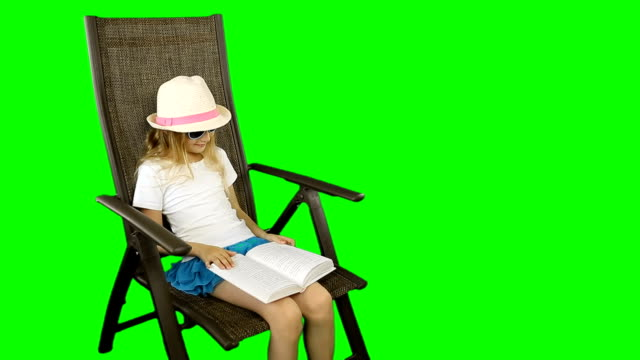 A young girl sits on a chair and reads a book laughing. video