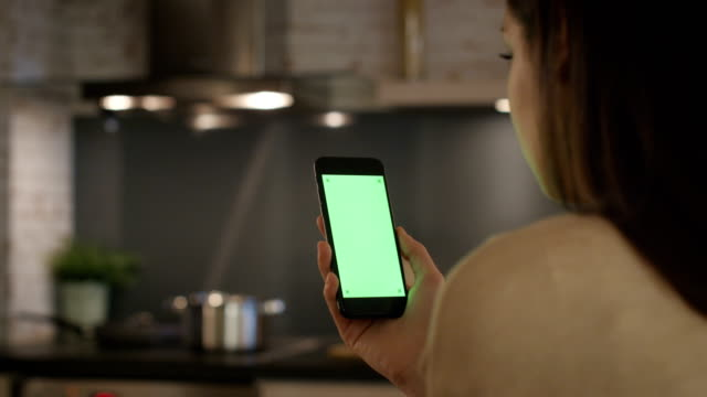young girl sitting in the kitchen using smartphone with green screen. - kitchen filmów i materiałów b-roll