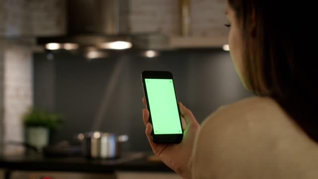 Mutfakta Yeşil perde ile Smartphone kullanarak oturan genç kız. video