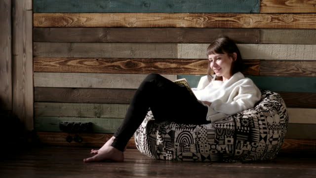 Young girl sitting on a chair and reading a book video