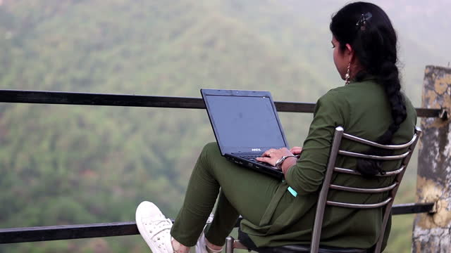 Young girl sitting on chair and she using laptop, Himachal Pradesh, India video