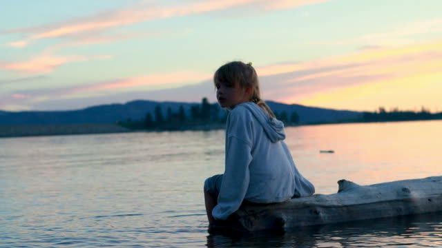 Young girl sitting on floating log on mountain lake at sunset video