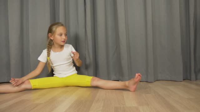 Young girl sitting on floor at living room. White girl stretchig and dancing. Girl do split indoors. video