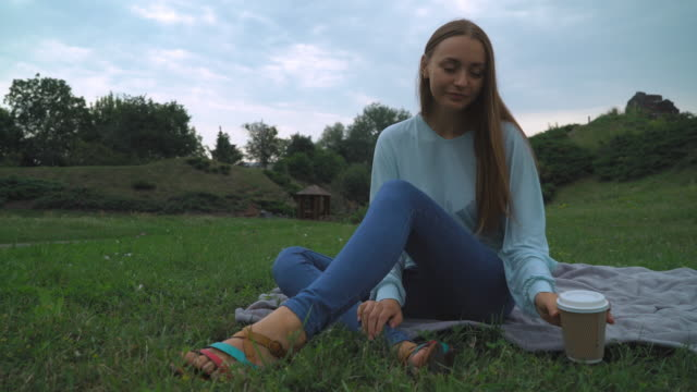 A young girl sitting on the lawn in the park and drink a glass of coffee video