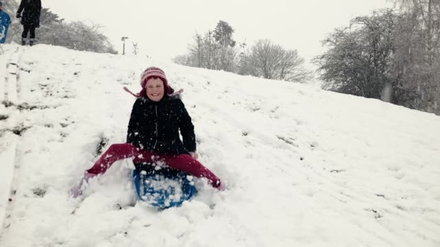 Young girl sledging and coming to a stop video