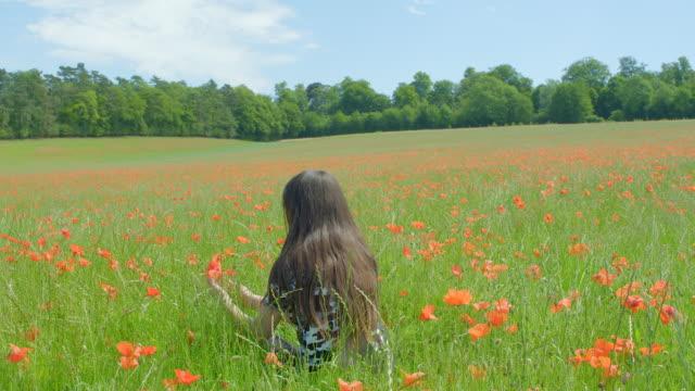 Ein junges Mädchen riecht eine Blume auf einer Wiese. – Video