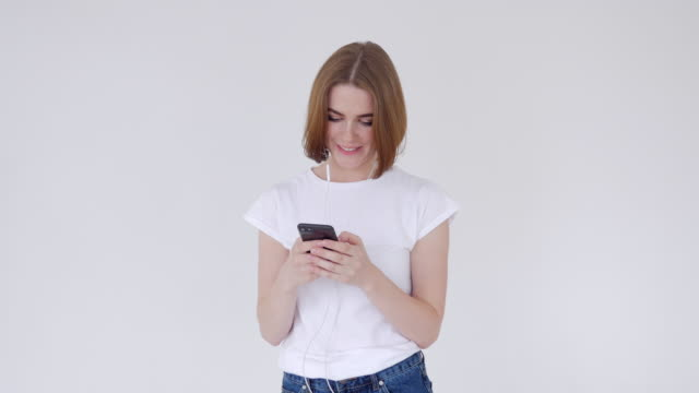 Young girl smiling while texting on cellphone Close-up of young girl smiling while texting on cellphone. Listen to music supermodel stock videos & royalty-free footage