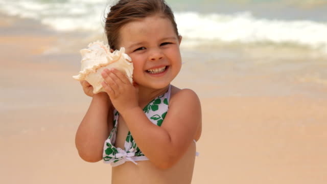 Young girl standing at beach holding shell up to ear video