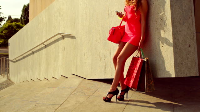 Young girl standing by the wall. Shopping video